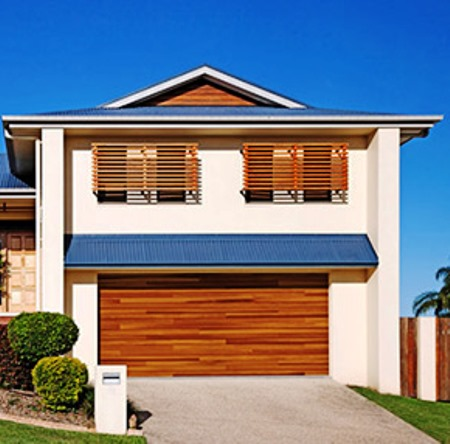 A home with a wooden garage door representing the garage door installation services of Aldor Sales, Inc. in Jacksonville, FL
