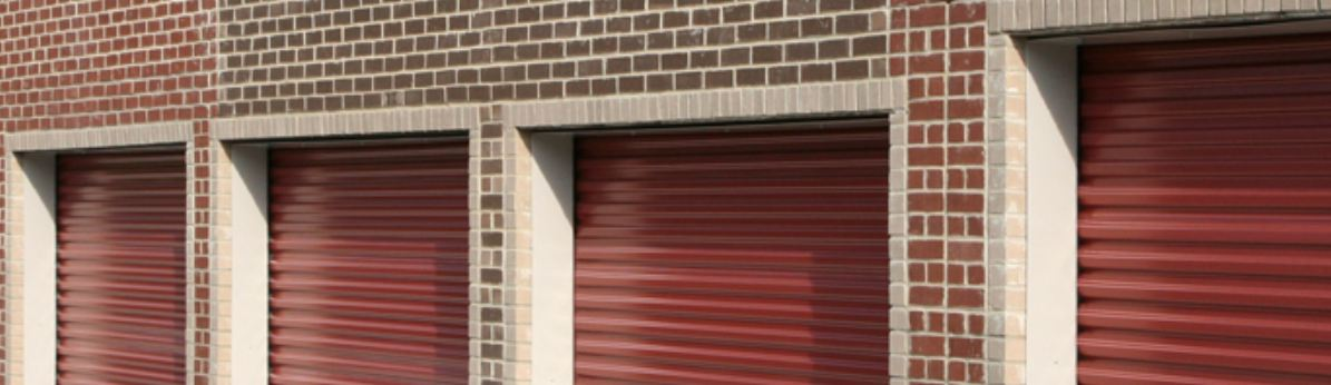 Red brick garage with red metal garage doors designed by residential garage door repair company Aldor Sales, Inc. In Jacksonville, FL