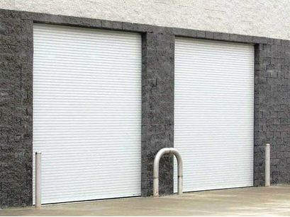 A white and grey garage representing the commercial garage door installation services of Aldor Sales, Inc. in Jacksonville, FL